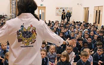 Mad Scientist at special event presenting to room full of children sitting on the floor