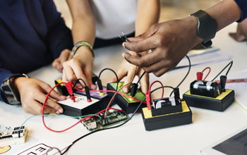 one hand holding tweezers while 2 others building electronics.  36 black and red wires plugged in to boards